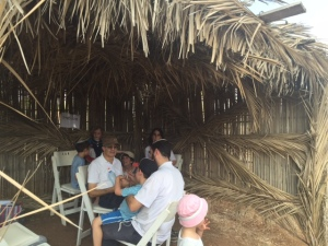 """The sukkah exhibit showed which types of sukkot are """"kosher"""" (okay to use) and which ones are not okay.  As I mentioned in my last post during the week of Sukkot one is supposed to sit in the sukkah for all meals.  Here is a family enjoying a picnic in one of the """"kosher"""" sukkahs."""