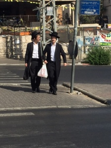 Walking home you can see these two men have a tall plastic bag between them, that holds the lulav.