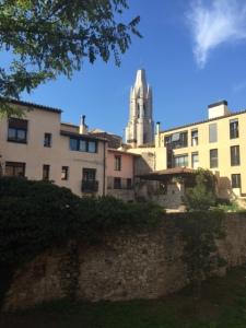You can see the tower of St. Feliu over modern apartment buildings and a reconstructed wall below.