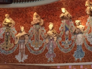 On both sides of the stage are figures with protruding heads and instruments in relief and mosaic bodies. There are nine female figures on each side.