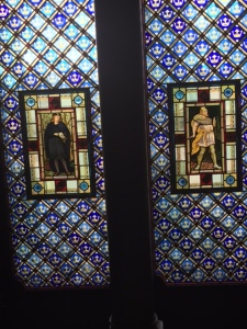 Stained glass window with Shakespearean characters in a pre-Raphaelite style and William Morris pattern (Arts and Crafts movement).
