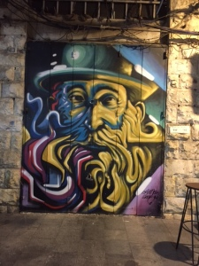 Machane Yehuda is a fabulous though gritty indoor market selling everything and anything. Two artists have taken upon themselves to spray paint portraits of famous Jewish figures on the metal shutters of every stall. It's a great visual late at night. If you want to know more I've attached a link.