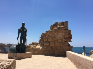 Wall of the breakwater of Caesarea with a modern Neptune like figure similar to one you can buy across the road.